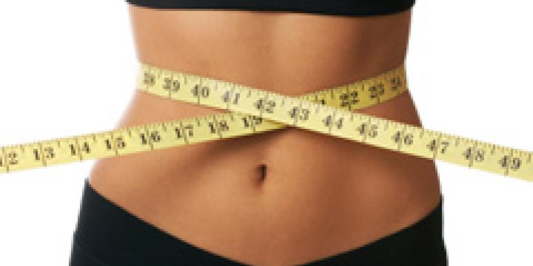 woman with a tape measure around her stomach