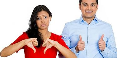 woman giving thumbs up while man gives thumbs down