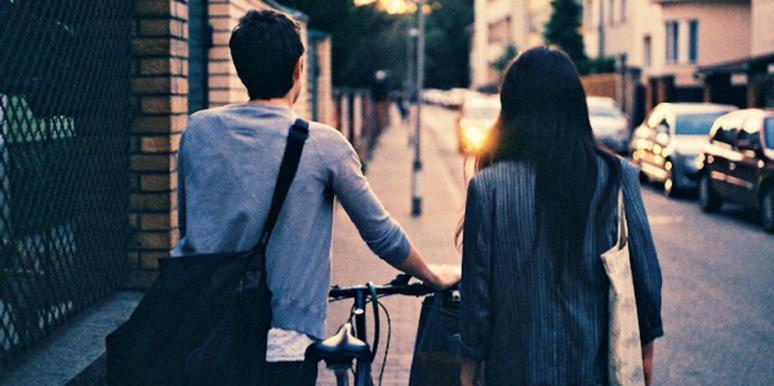 couple walking with bike