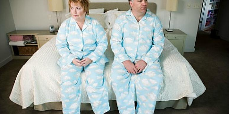 couple sitting on bed in matching pajamas