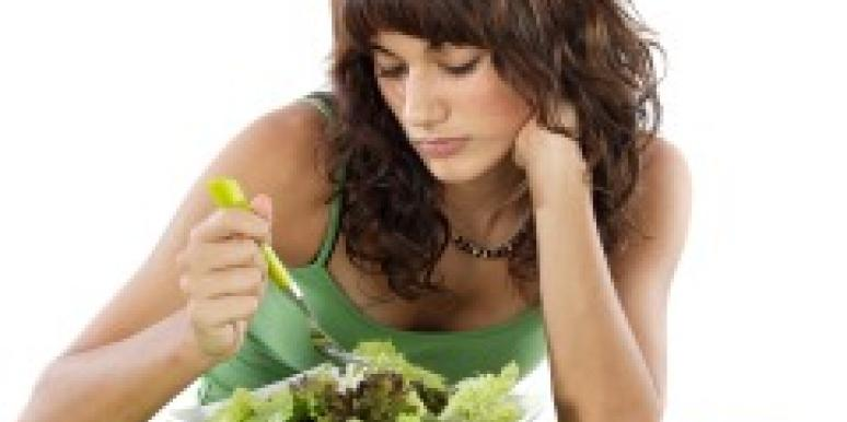 Sad woman staring at salad