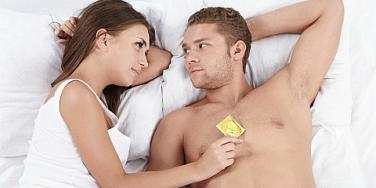 man and woman lying in bed with condom