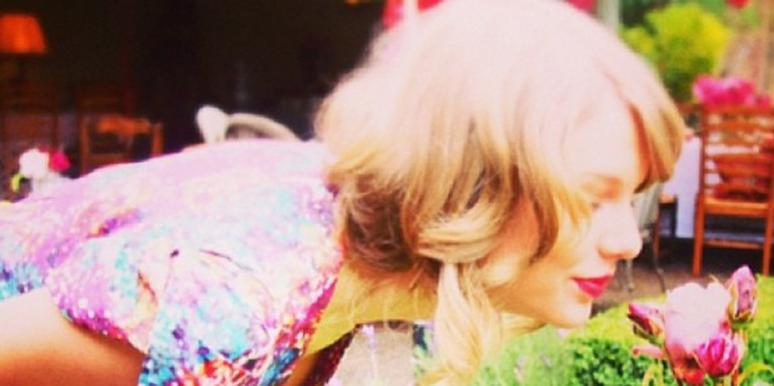 Taylor Swift bending over to smell a flower