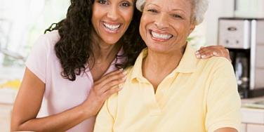 adult daughter with elderly mother smiling