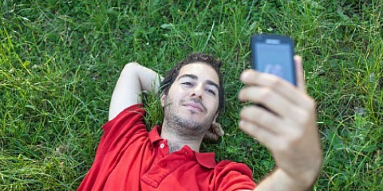 man lying on the grass taking selfie