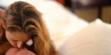 caucasian couple kissing in bed with bedroom out of focus