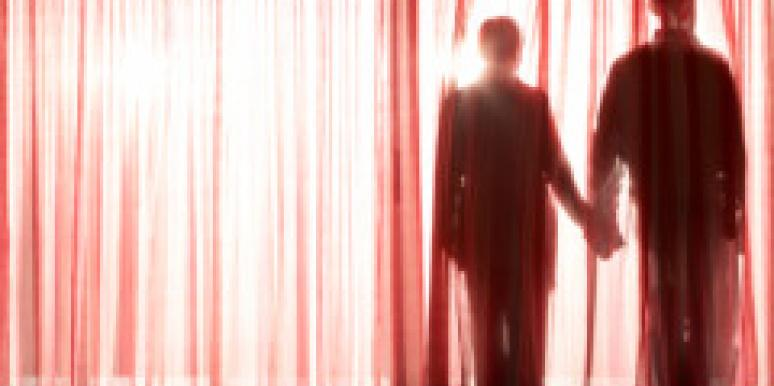 shadow of couple holding hands behind sheer red curtain