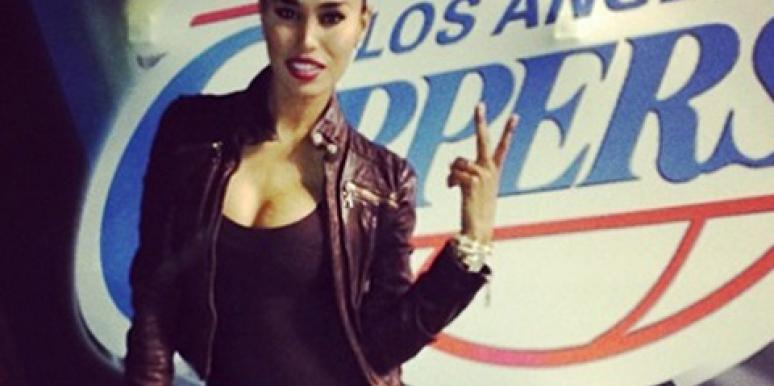 V Stiviano in front of a Los Angeles Clippers logo