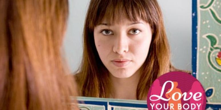 young woman with bangs looking in mirror