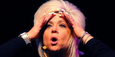 "Theresa Caputo, the self-professed ""Long Island Medium"" of TLC stardom, holding her head in her hands and looking shocked"