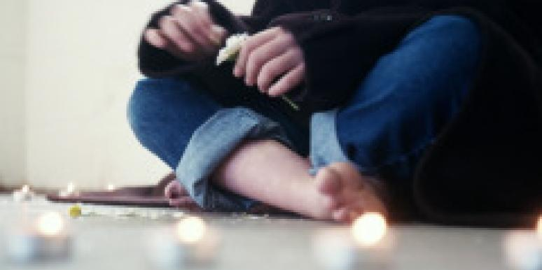 seated cross legged with lit candles on the floor
