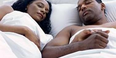 pregnant couple in bed sleeping
