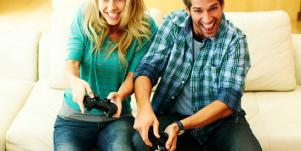 man woman playing video games on sofa