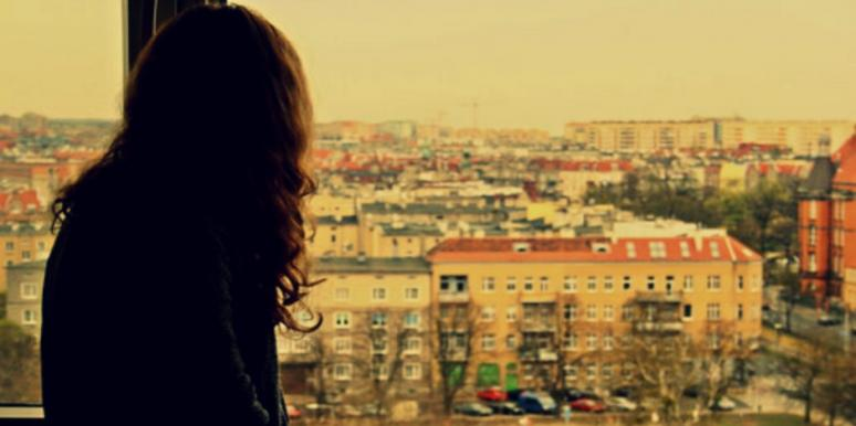 woman staring out of her window