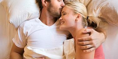 man kissing woman's forehead in bed