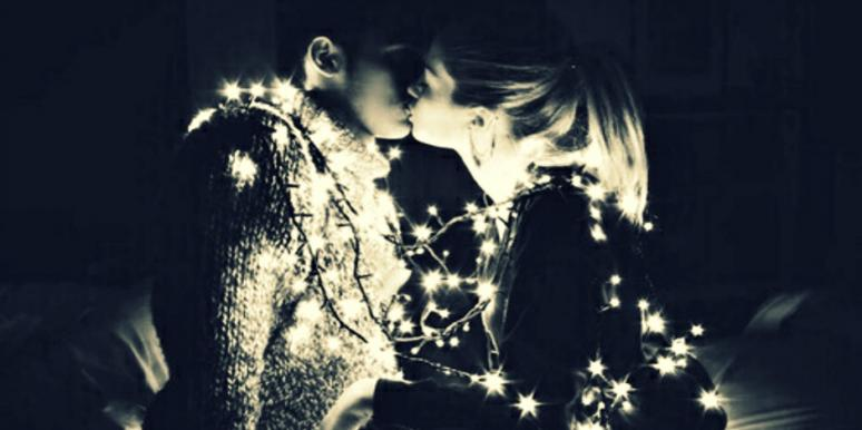 couple kissing around christmas tree lights