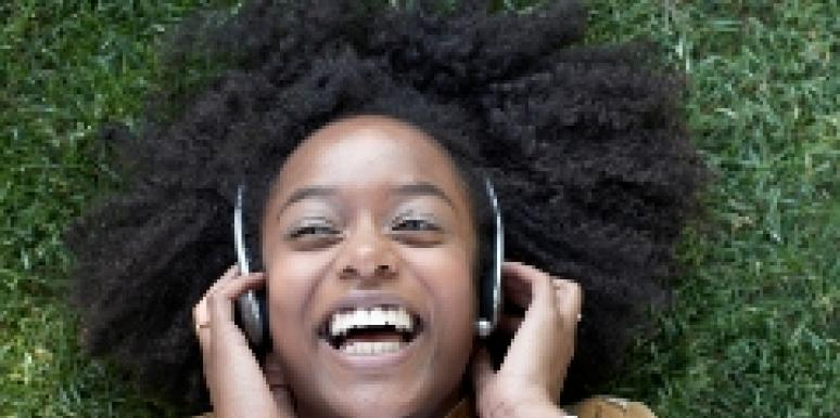 A woman happily listens to music.