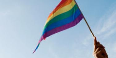 woman waving ranbow flag in the air