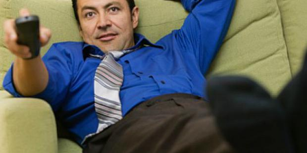 man wearing a tie on the sofa with a TV remote