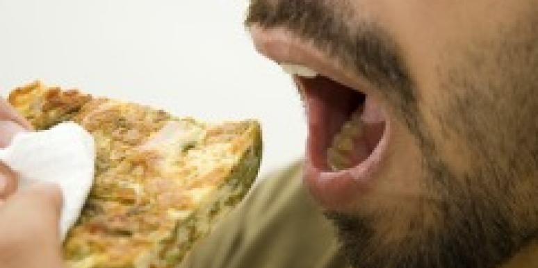 Man's mouth eating a piece of bread
