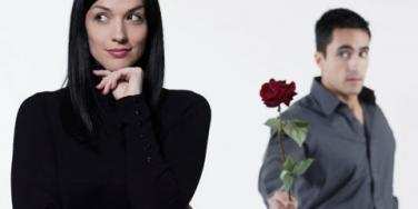 man offering rose to woman