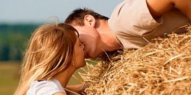 couple kissing by haystack