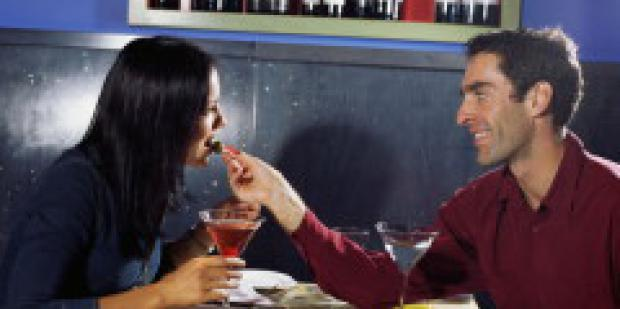 Man feeding a woman olives on a date