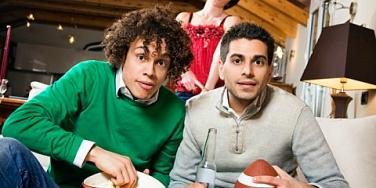 Two men watch football with woman in the background