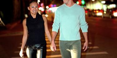young attractive couple holding hands across street