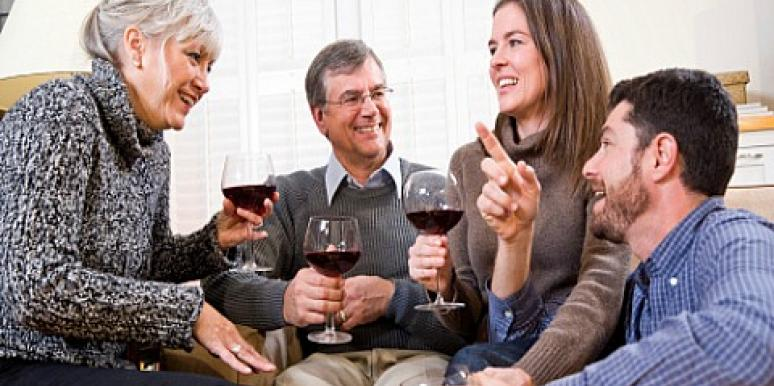 young couple having wine with older couple