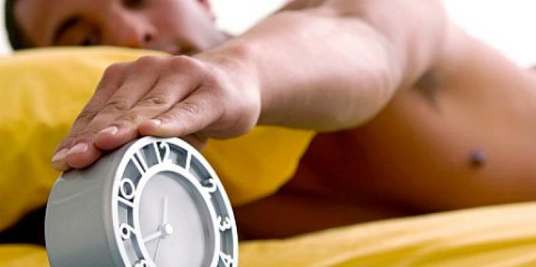 man touching alarm clock