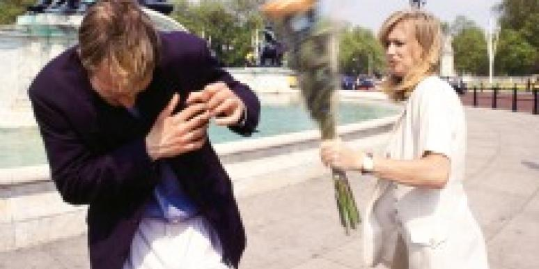 Woman hitting a man with a bouquet of flowers