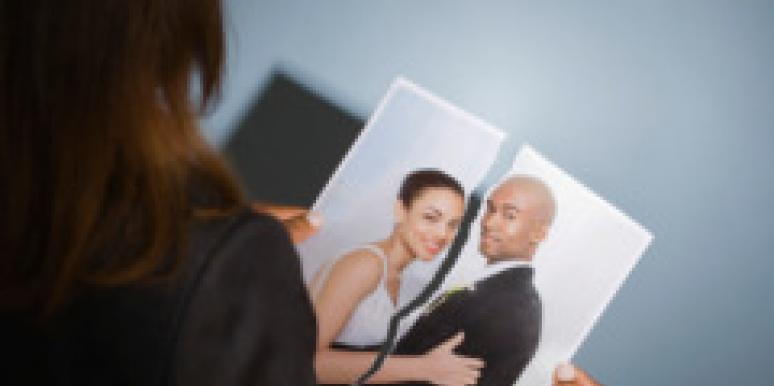 woman holding torn photo of couple