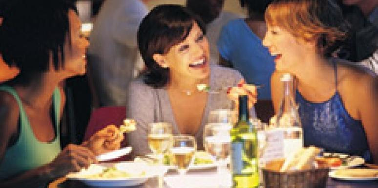 women female friends laughing at dinner