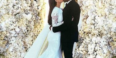 Kim Kardashian and Kanye West kissing at their wedding in front of a wall of roses, from Kardashian's Instagram account