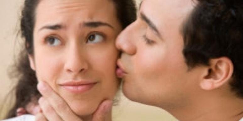 man kissing woman's cheek