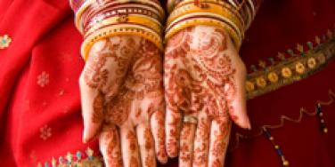 Henna on the hands of an Indian woman wearing jewelry